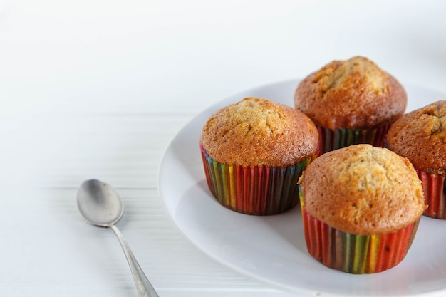Cupcakes caseros en un plato con una cuchara sobre la mesa de madera blanca