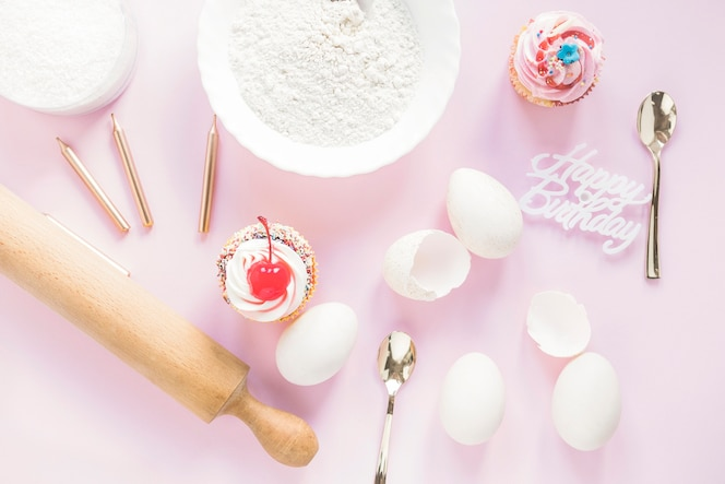 Cupcakes cerca de los ingredientes de la torta de cumpleaños
