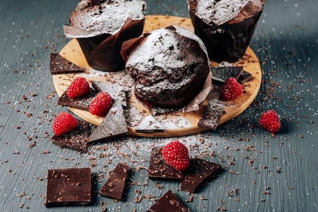Cupcakes de chocolate de cerca con chocolate y frambuesas