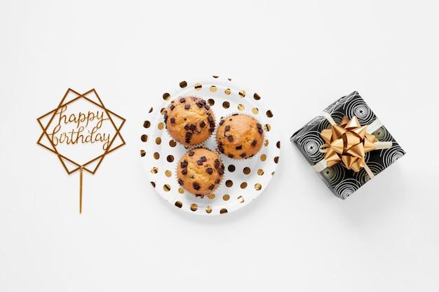 Cupcakes de cumpleaños y presente sobre fondo blanco.