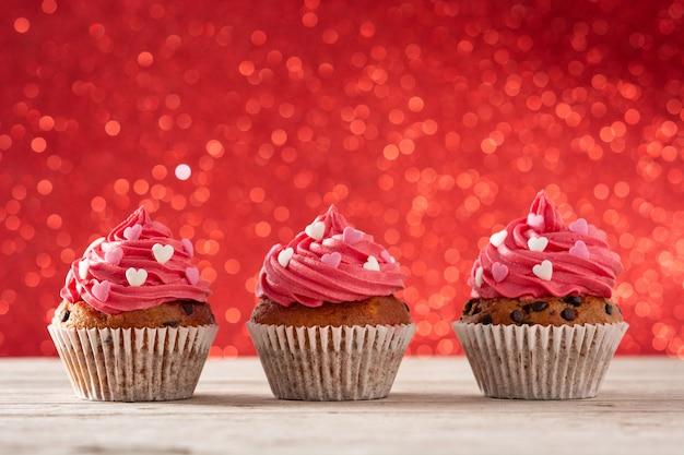 Cupcakes decorados con corazones de azúcar para el día de san valentín en mesa de madera y fondo rojo.