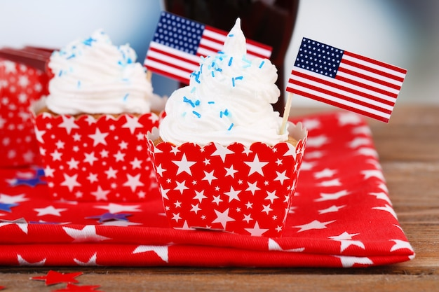 Cupcakes de fiesta patriótica americana y vaso de cola en la mesa de madera