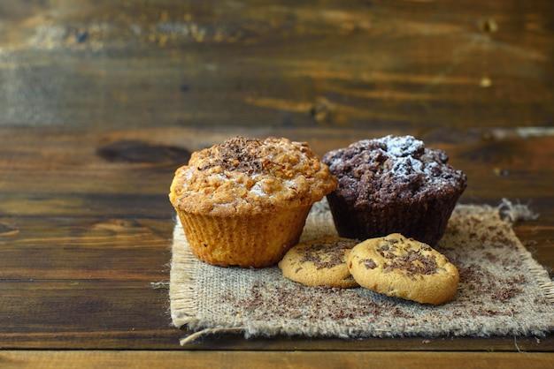 Cupcakes y galletas con chocolate sobre fondo de madera oscura.