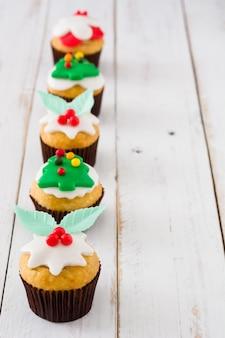 Cupcakes de navidad en el espacio de copia de mesa de madera blanca