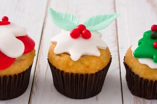 Cupcakes de navidad en mesa de madera blanca de cerca
