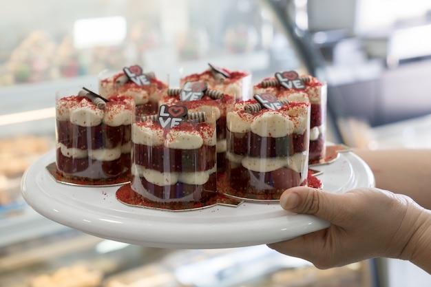 Cupcakes de terciopelo rojo con queso crema glaseado en mano