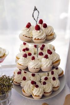 Los cupcakes terminados con crema blanca y frambuesas en la parte superior del soporte el día de