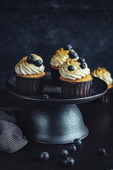 Cupcakes de vainilla con arándanos en placa oscura sobre superficie oscura