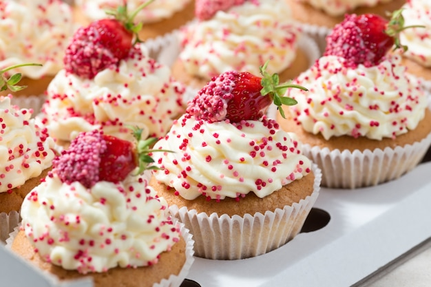 Cupcakes de vainilla decorados con fresas frescas en caja de entrega