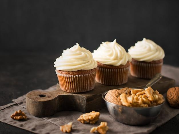 Cupcakes de zanahoria o muffins con nueces sobre negro