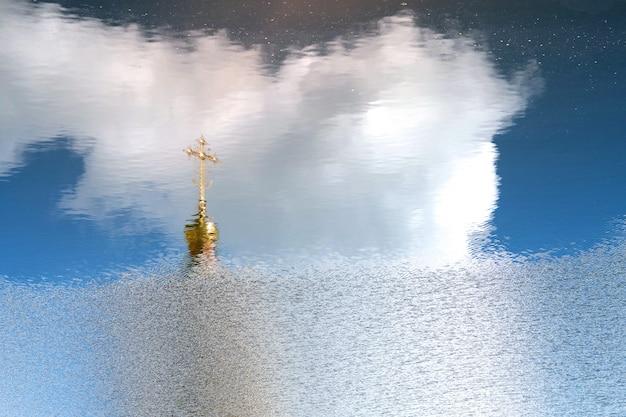 Cúpula dorada y cruz ortodoxa reflejada en la superficie del agua.
