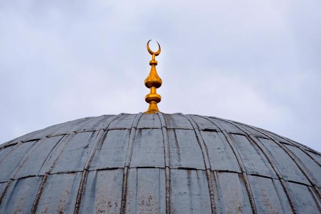 Cúpula rústica vintage de una antigua mezquita con una luna creciente dorada, arquitectura islámica