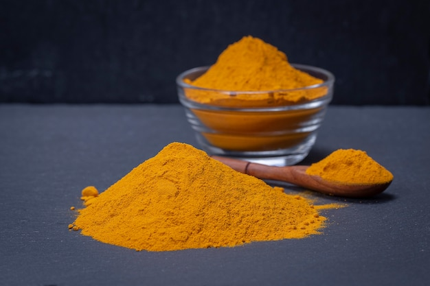 Cúrcuma orgánica, cúrcuma en polvo sobre fondo de plato de pizarra negra. polvo de curry. de cerca