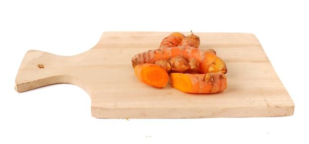 Cúrcuma en una tabla para cortar madera aislado sobre un fondo blanco.