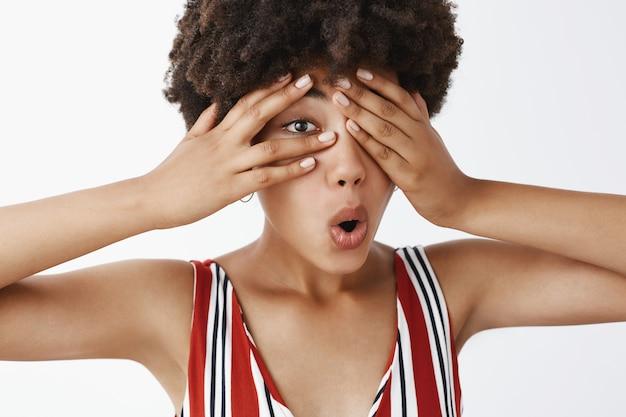 Curiosa y atractiva modelo femenina de piel oscura con peinado afro en ropa a rayas cubriendo los ojos con las palmas y mirando a través de los dedos con interés doblando los labios, intrigada