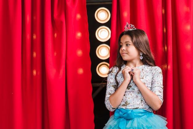 Curiosa chica linda de pie delante de la cortina roja mirando el escenario