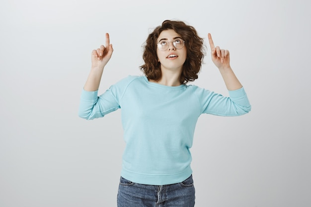 Curiosa chica soñadora mirando y señalando con el dedo hacia arriba