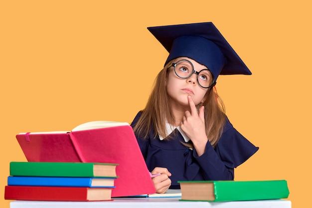 Curiosa colegiala en traje de graduación estudiando con libros de texto