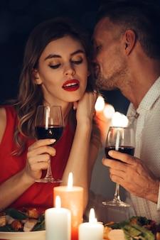 Curiosa dama en vestido rojo con copa de vino escuchando a su hombre guapo