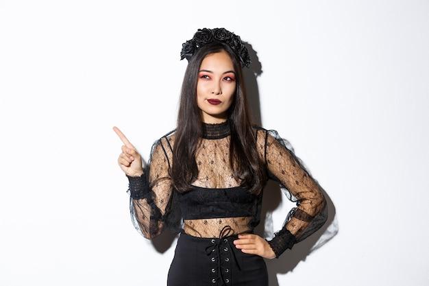 Curiosa mujer asiática atractiva en traje de bruja, apuntando con el dedo en la esquina superior izquierda, mirando interesada en la promoción de halloween, de pie sobre la pared blanca y pensando