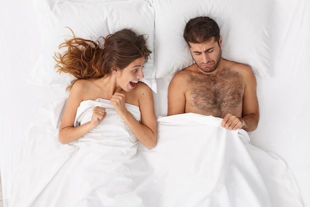 Curiosa mujer emocionada mira los genitales del hombre mientras se acuestan juntos en la cama. el hombre disgustado mira el pene bajo una manta blanca, sufre de disfunción sexual. problemas sexuales, matrimonio, concepto de relación