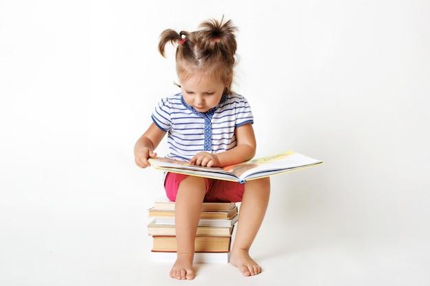 Curiosa niña con dos colas de caballo divertidas, se sienta en una pila de libros, lee un cuento de faity interesante, ve imágenes coloridas con gran interés, aprende a leer aislado en el estudio blanco.
