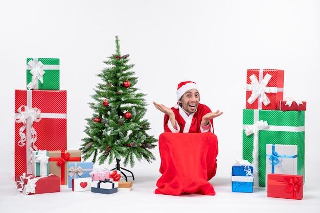 Curioso joven emocional feliz vestido como papá noel con regalos y árbol de navidad decorado sobre fondo blanco.