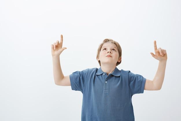 Curioso niño rubio despreocupado con camiseta azul, levantando las manos, mirando y apuntando hacia arriba con los dedos índices, disfrutando de hermosas estrellas y haciendo preguntas a mamá