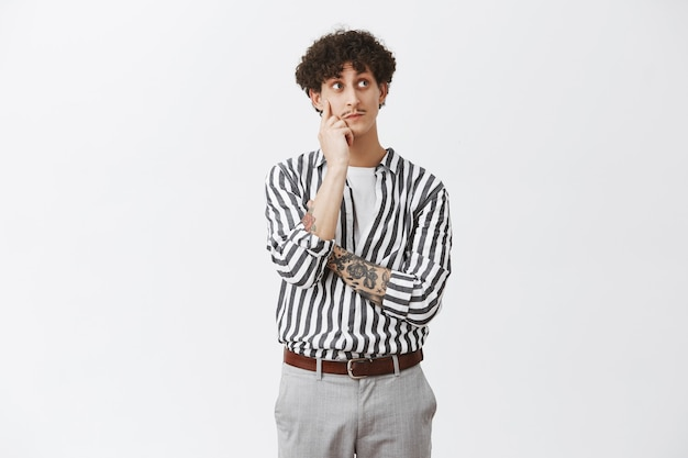 Curioso, pensativo y lindo chico judío con cabello oscuro y rizado y bigote sosteniendo la mano en la cara mientras piensa mirando en la esquina superior derecha curiosamente viendo algo interesante sobre la pared gris