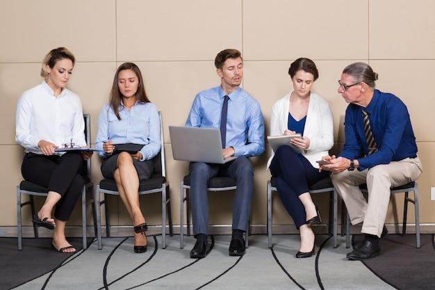 Curiosos gente de negocios sentado en sala de espera