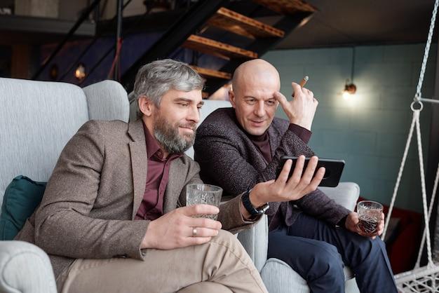 Curiosos hombres guapos de mediana edad bebiendo whisky y viendo videos en línea usando un teléfono inteligente