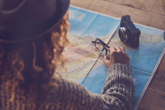 Curly lady vista desde la parte trasera planeando el próximo viaje vacaciones pasión por los viajes en un mapa de papel y una vieja cámara sobre la mesa - planificación de vacaciones y concepto de viaje para personas hipster en casa - pasión por los viajes y tenerife