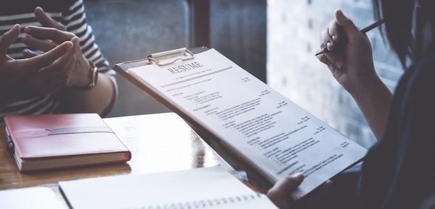 Currículum de lectura empresaria del hombre en el documento durante una entrevista