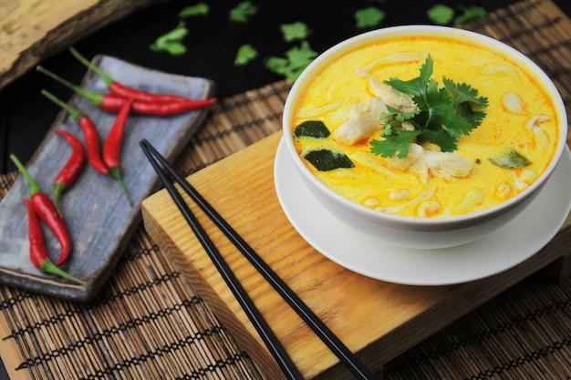 Curry amarillo con pollo, en tazón blanco y palillos