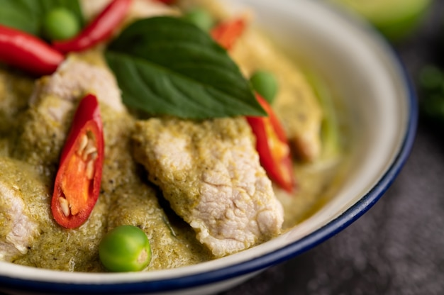 Curry de cerdo verde en un recipiente blanco con especias sobre un fondo de cemento negro