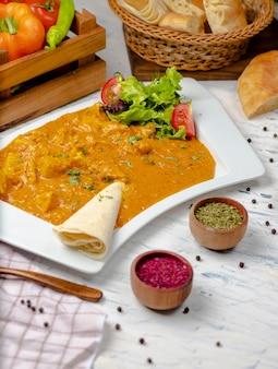 Curry indio con pechuga de pollo y salsa de tomate servido con lavash.
