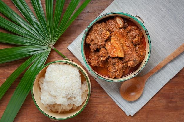 Curry rojo con carne de cerdo en portaaviones en la mesa de madera, comida tailandesa septentrional.