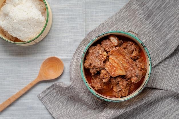 Curry rojo con cerdo en el transportador de alimentos, comida tailandesa septentrional.
