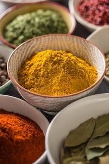 Curry y variedad de especias y hierbas en tazones.