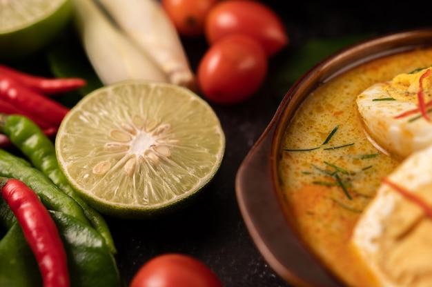 Curry verde con huevos en tazas negras, con limón, limoncillo, ají y tomates.