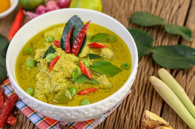 Curry verde en un tazón con lima, cebolla roja, hierba de limón, ajo y hojas de lima kaffir