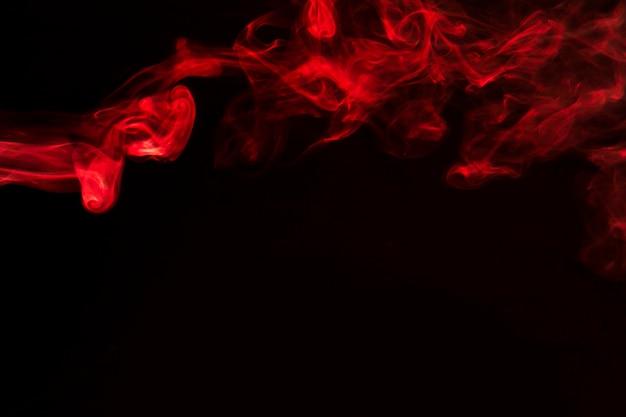 Curvas y onda abstractas rojas del humo en fondo negro