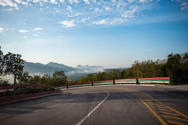 Curve el camino que conduce un coche en el camino de la montaña cuesta abajo. curva dramática hermosa nube de cielo azul con niebla de niebla en la mañana.