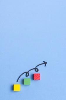 Curvy line arrow apuntando hacia arriba y cubos de colores