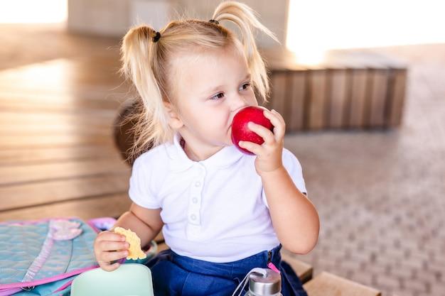 Cute adorable niño caucásico bebé niña sentada y comiendo