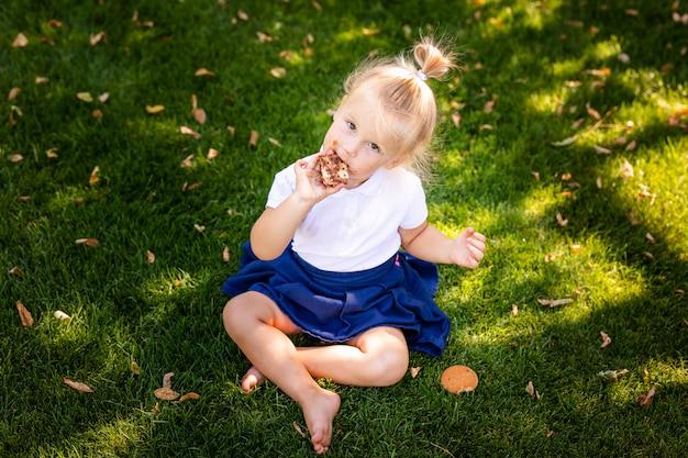 Cute adorable niño caucásico niña sentada y comiendo bayas frutas
