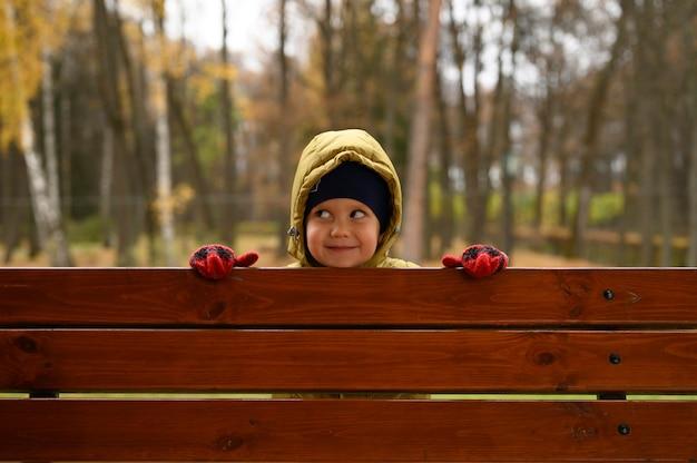 Cute little baby boy se divierte en el parque otoño