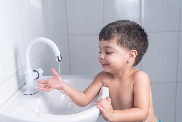 Cute little baby boy lavarse las manos en el lavabo del baño