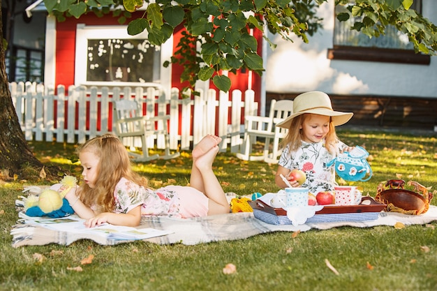Cute little blond girls leyendo libro afuera sobre la hierba