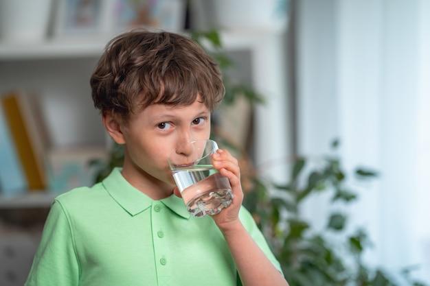 Cute little boy agua potable en casa balance de agua